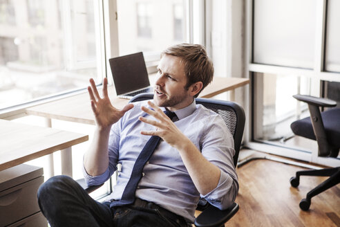 Businessman gesturing while sitting on chair at office - CAVF08942