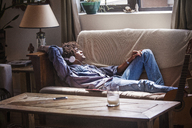 Man listening music while relaxing on sofa at home - CAVF09032