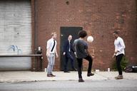 Happy friends playing soccer on street - CAVF09053