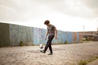 Man juggling soccer ball on footpath - CAVF09065