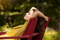 Side view of woman relaxing on lounge chair - CAVF09119