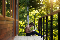 Boy reading book while sitting by railing in balcony - CAVF09125