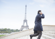 Businessman talking on cell phone and ascending steps near Eiffel Tower, Paris, France - CAIF17014