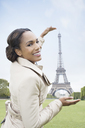 Woman posing as if to hold Eiffel Tower, Paris, France - CAIF17026