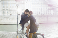 Couple hugging on bicycle along Seine River, Paris, France - CAIF17029