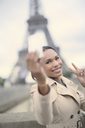 Woman taking picture in front of Eiffel Tower, Paris, France - CAIF17032