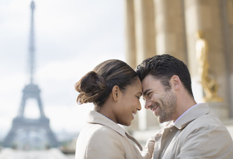 Couple hugging in front of Eiffel Tower, Paris, France - CAIF17035