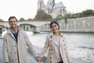 Couple holding hands along Seine River near Notre Dame Cathedral, Paris, France - CAIF17059