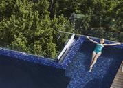 Woman floating in luxury swimming pool - CAIF17086