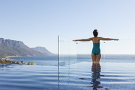 Woman basking in infinity pool overlooking ocean - CAIF17089