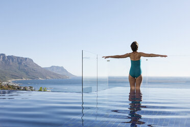 Woman basking in infinity pool overlooking ocean - CAIF17089