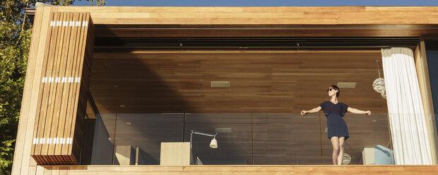 Woman standing on luxury balcony - CAIF17110
