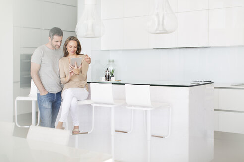 Couple using digital tablet in kitchen - CAIF17134