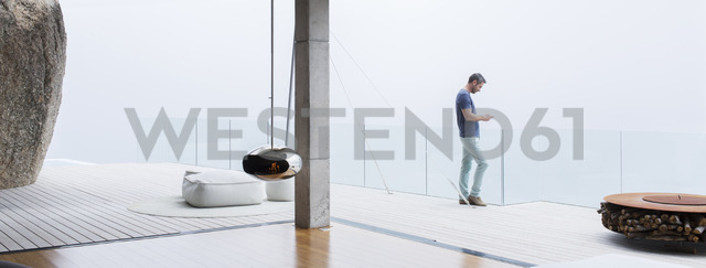 Man using cell phone on balcony of modern house - CAIF17137 - Astronaut Images/Westend61