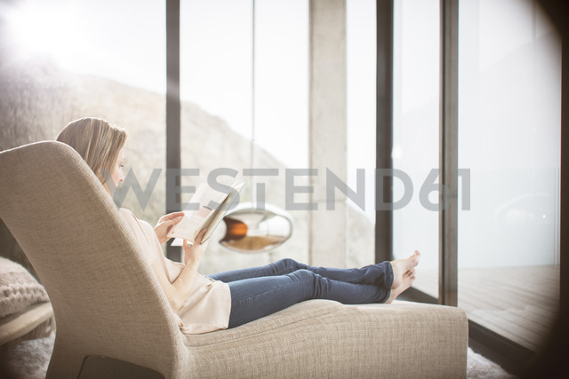 Woman reading on sofa in modern living room - CAIF17140