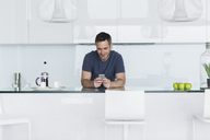 Man using cell phone in modern kitchen - CAIF17149