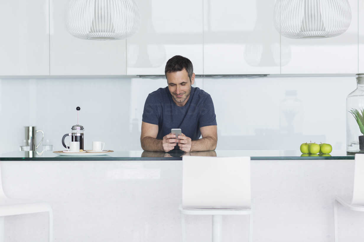 Man using cell phone in modern kitchen - CAIF17149 - Astronaut Images/Westend61