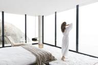 Woman wearing bathrobe in modern bedroom - CAIF17158