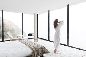 Woman wearing bathrobe in modern bedroom - CAIF17158