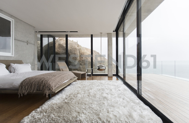 Shag rug and glass walls in modern bedroom - CAIF17164 - Astronaut Images/Westend61