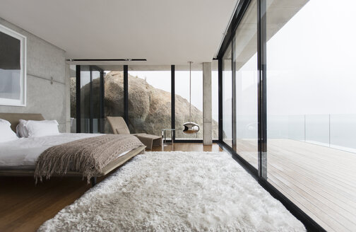 Shag rug and glass walls in modern bedroom - CAIF17164