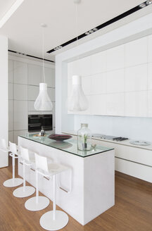 Bar stools at counter in modern kitchen - CAIF17167