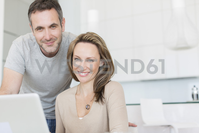 Couple smiling at laptop - CAIF17173