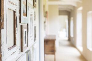 Decorative wall frames in rustic hallway - CAIF17185