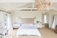 Chandelier and bed in rustic bedroom - CAIF17194