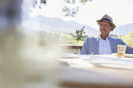 Older man sitting at outdoor dinning table - CAIF17288