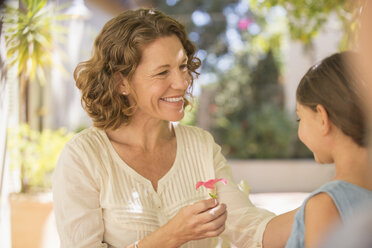 Grandmother offering granddaughter pink flower - CAIF17294
