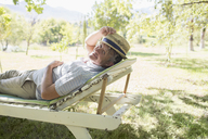 Older man relaxing on lawn chair outdoors - CAIF17300