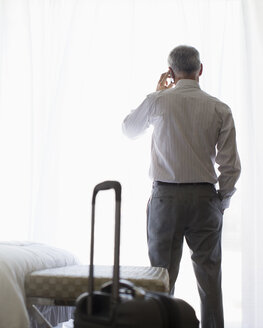 Businessman talking on cell phone in hotel room - CAIF17381