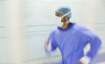 Male surgeon rushing through hospital corridor - CAIF17404
