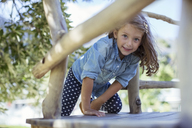 Girl climbing in treehouse outdoors - CAIF17452