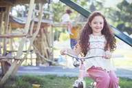 Smiling girl sitting on bicycle at playground - CAIF17464