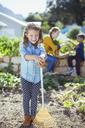 Girl holding rake in garden - CAIF17476