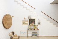 Side table and wall hangings by staircase - CAIF17545