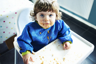 Messy baby girl eating in high chair - CAIF17557