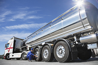 Worker checking tire on stainless steel milk tanker - CAIF17584