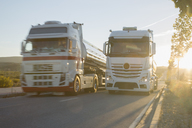 Stainless steel milk tankers on the road side by side - CAIF17590