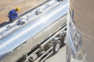 Worker on platform above stainless steel milk tanker - CAIF17593