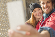 Couple taking self-portrait with camera phone next to chain link fence - CAIF17665