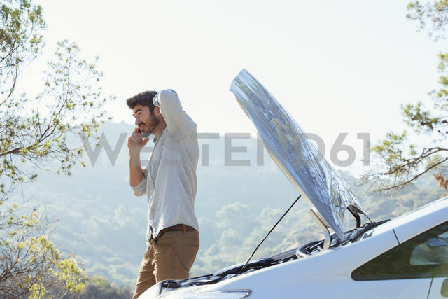 Man talking on cell phone with automobile hood raised at roadside - CAIF17680
