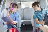 Happy brother and sister with headphones using digital tablets in back seat of car - CAIF17689