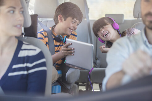 Happy brother and sister using digital tablet in back seat of car - CAIF17692