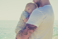 Close up of father holding baby son at beach - CAIF17695