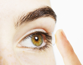 Extreme close up of woman putting contact lens into eye - CAIF17713