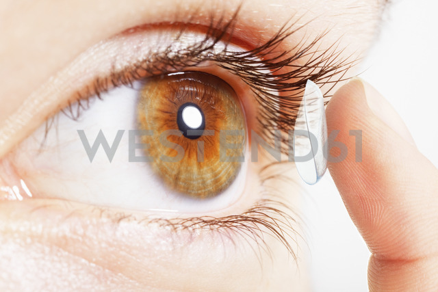 Extreme close up of girl putting contact lens in eye - CAIF17716