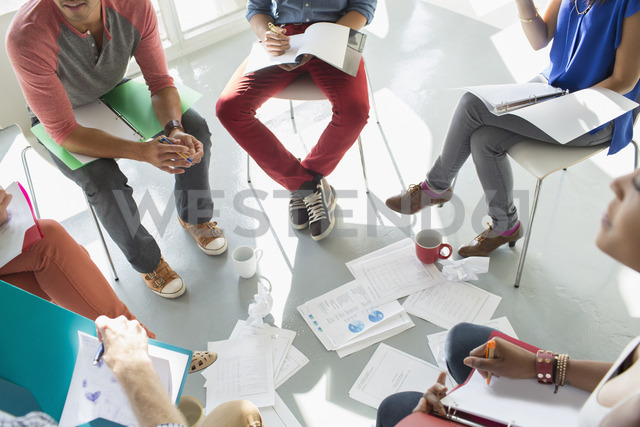 Creative business people meeting with coffee and paperwork in circle of chairs - CAIF17737